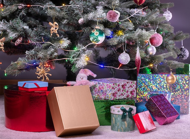 Boxes of presents under decorated artificial christmas tree.