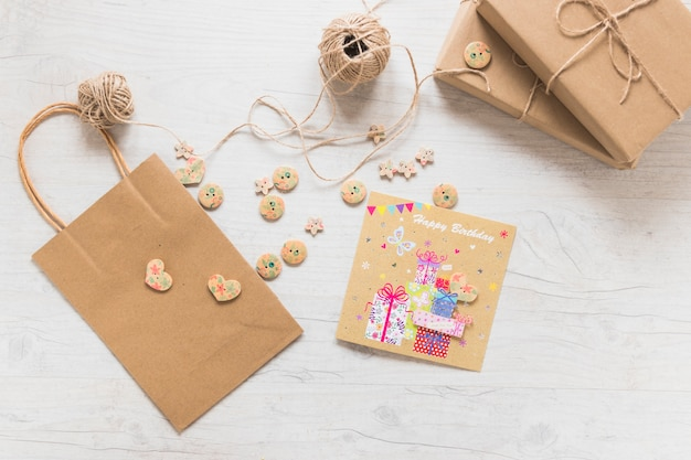 Boxes; string spool; paper shopping bag; buttons and birthday greeting card on white textured background
