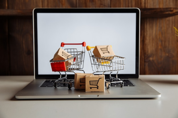 Boxes in a trollies on a laptop keyboard. online shopping concept.