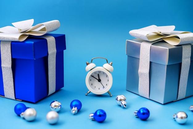 Коробки с подарками и елочные синие игрушки с часами, концепция времени рождественских праздников