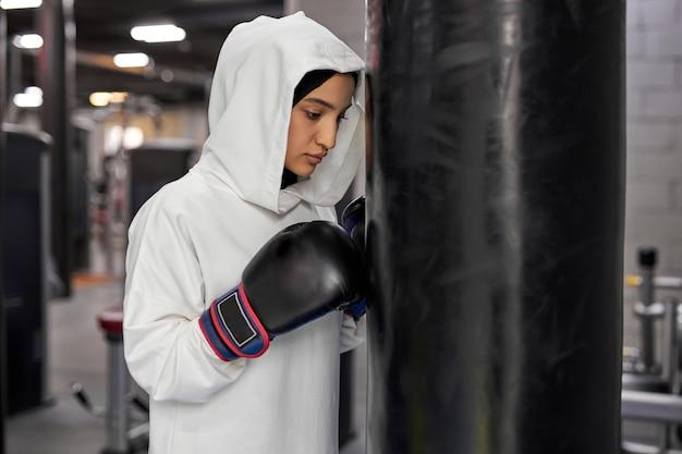 サンドバッグのそばに立っている白いヒジャーブまたはイスラムのスポーツウェアのボクシングアスリートイスラム教徒の女性、アラビアフィットの女性が戦うつもりであり、深刻な顔で立っています。ジムの屋内