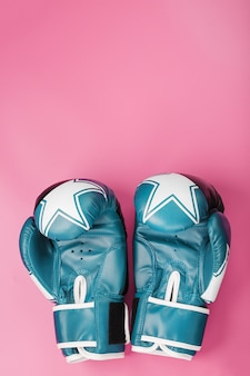 Boxing blue gloves on a pink background
