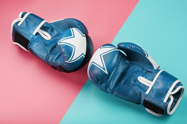 Boxing blue gloves on a pink and blue background diagonally
