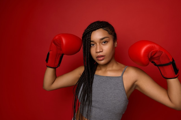 Boxing chamion afro girl, athlete woman boxer wearing red gloves, raising her hands up, looking at camera, isolated over red colored background with copy space. contact martial art and victory concept