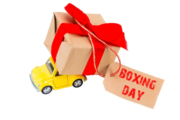 The boxing day concept. yellow retro toy car delivering gifts box with tag with text boxing day on white background.