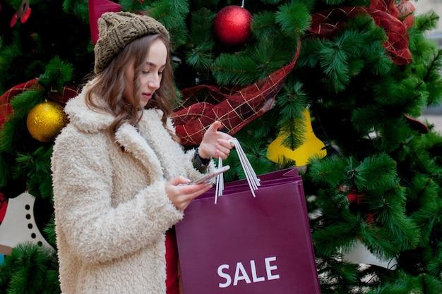 День подарков. покупка товаров и подарков. покупки для семьи. рождественские продажи концепции. женщина, держащая подарок хозяйственной сумки xmas. большая скидка.