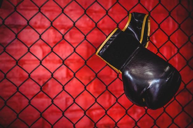 Боксерская перчатка висит на заборе из проволочной сетки