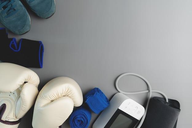 ボクシンググローブ、血圧計、コピースペースと灰色の背景にフィットネス機器