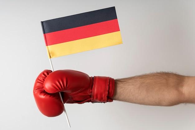 ドイツ国旗のボクシンググローブ。ボクサーはドイツの旗を保持しています。白色の背景。