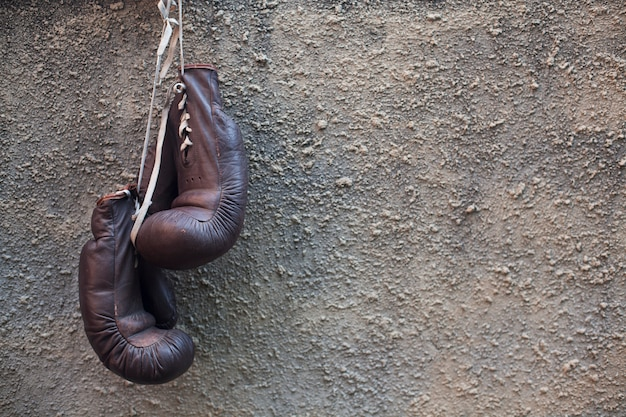 Boxing gloves hanging on cement wall