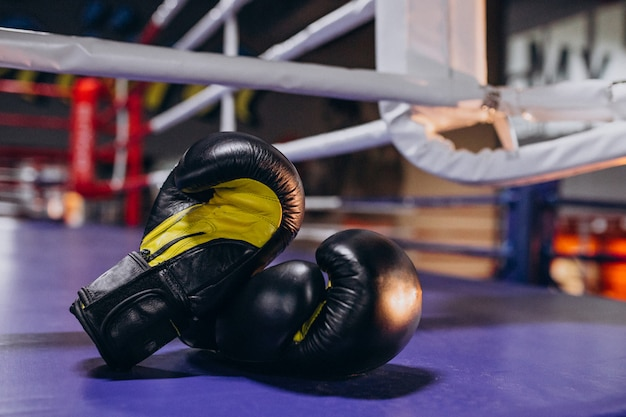 Боксерские перчатки лежат на пустом ринге