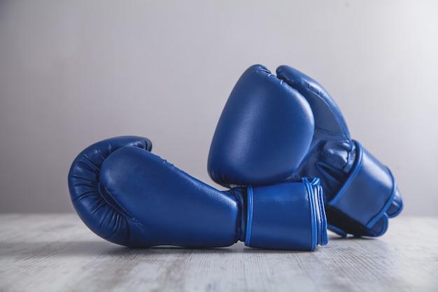 Боксерские перчатки на белом современном столе.