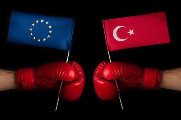 欧州連合とトルコの旗が付いているボクシンググローブ。トルコと欧州連合の対立と関係の概念。