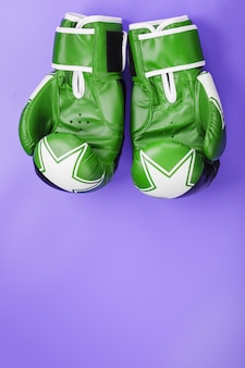 Boxing green gloves on a lilac background.