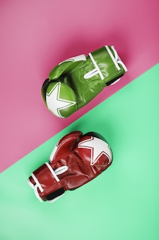 Boxing green and red gloves on a pink and blue background diagonally
