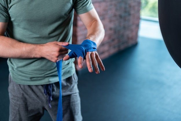 Boxing in gym. handsome strong muscle man using professional blue wrist wraps before boxing in gym