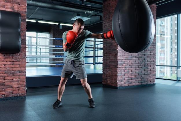 Бокс упорный. сильный профессиональный опытный спортсмен в серых шортах и рубашке цвета хаки боксирует в жестких красных перчатках