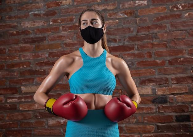ボクシング。フェイスマスクを身に着けているレンガの壁の背景にトレーニングプロの女性アスリート。世界的大流行のコロナウイルスの検疫中のスポーツ。機器を使用して安全なジムで練習している若い女性。