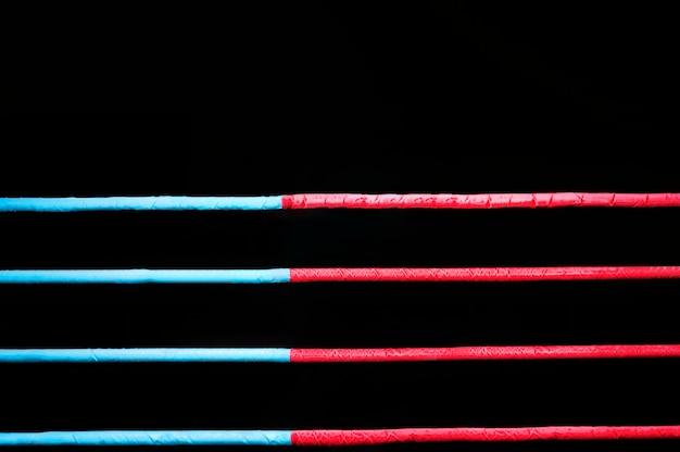 Канаты боксерского ринга на черном фоне. понятие о спорте, смешанных единоборствах. смешанная техника