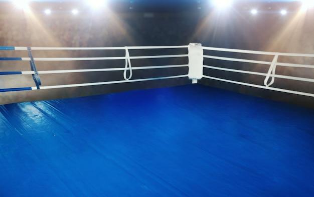 파란색 바닥과 흰색 로프가있는 복싱 링. 스포츠 대회 및 격투 토너먼트를위한 전문 경기장