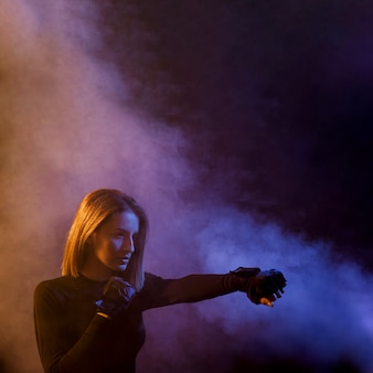 Boxing woman posing in smoke