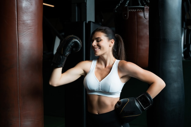 Boxing woman posing with punching bag, on dark gym. strong and independent woman concept
