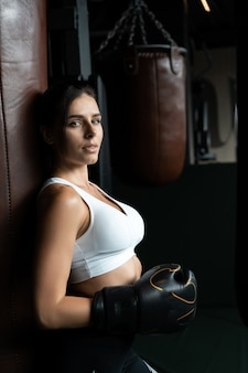 Boxing woman posing with punching bag, on dark . strong and independent woman concept
