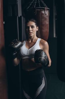 Бокс женщина позирует с боксерской грушей, на темном фоне. сильная и независимая концепция женщины