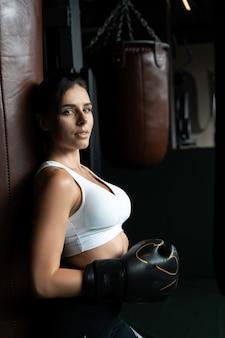 권투 여자 어둠에 샌드 백 포즈. 강력하고 독립적 인 여성 컨셉