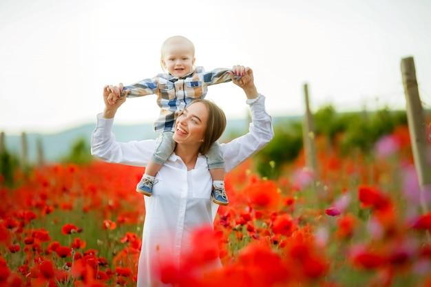 Мальчик 2 лет садится на шею матери и разворачивает руки, как самолет, во время веселой игры