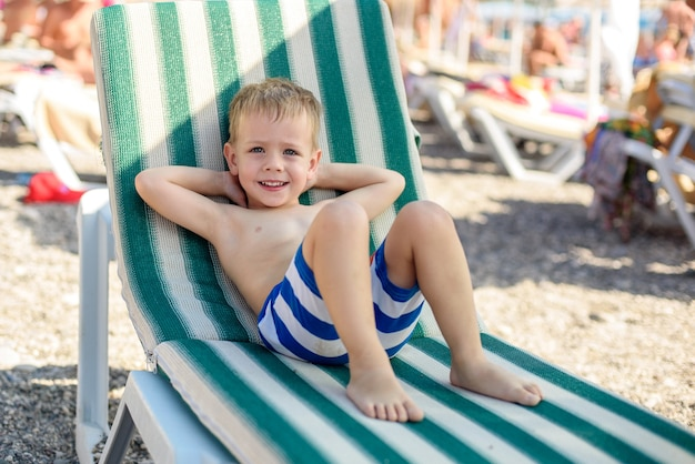 A boy of 4 years old in striped shorts lies on a sunbed on the beach contented and happy summer