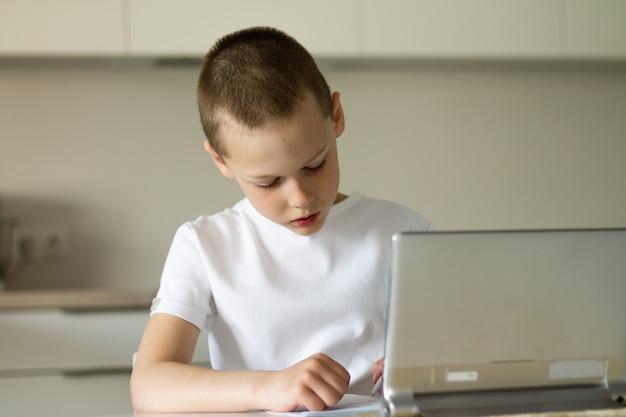 Мальчик 6-10 лет завершает школьные уроки и выполняет домашнее задание онлайн на кухне, глядя на планшетный компьютер. концепция дистанционного образования. оставайся дома.