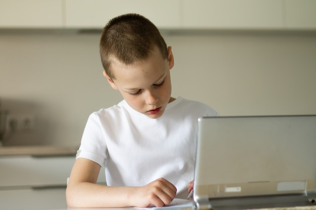 Boy 6-10 completes school lessons and homework online in the kitchen, looking at the tablet computer. the concept of distance education. stay at home.