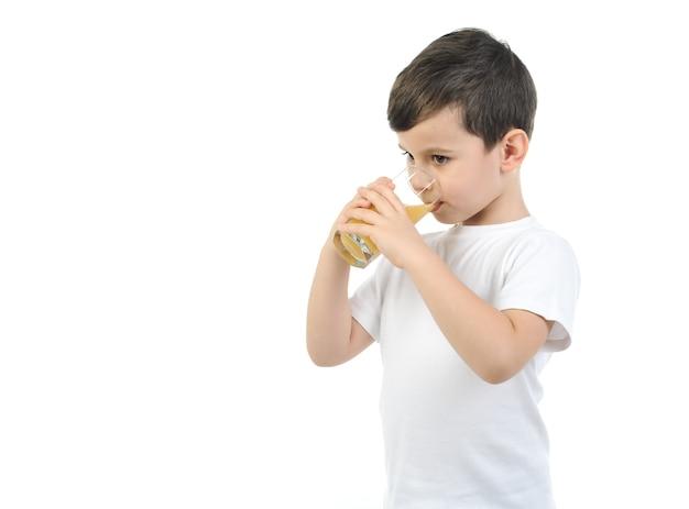 白いtシャツを着た6歳の少年は、白い背景に柑橘類のジュースを飲みます。孤立した背景。