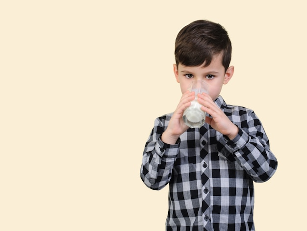 Boy 6 years old in a gray checkered shirt drinks milk from a glass on studio beige background