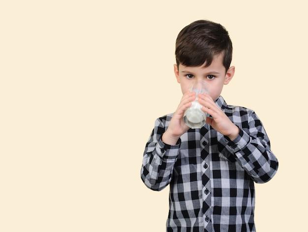 灰色の市松模様のシャツを着た6歳の少年は、スタジオベージュの背景にガラスからミルクを飲みます