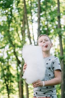 Мальчик 7-10 ест сладкую вату в солнечном парке среди высоких деревьев на зеленой траве. вертикальный