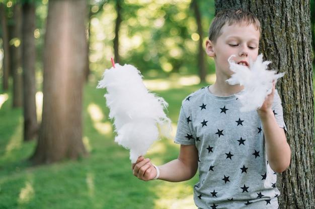 Мальчик 7-10 ест сладкую вату в солнечном парке среди высоких деревьев на зеленой траве
