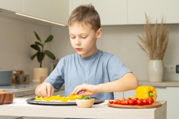 부엌에서 피자를 요리하는 티셔츠에 소년 7-10. 아이가 피자베이스에 재료를 준비