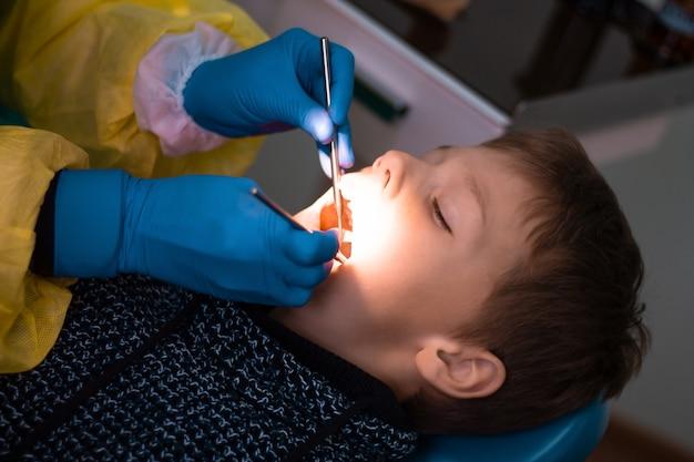 歯科医の椅子に座っている少年7-11と、歯科検診または歯科治療中に青い手袋をはめた医師の手