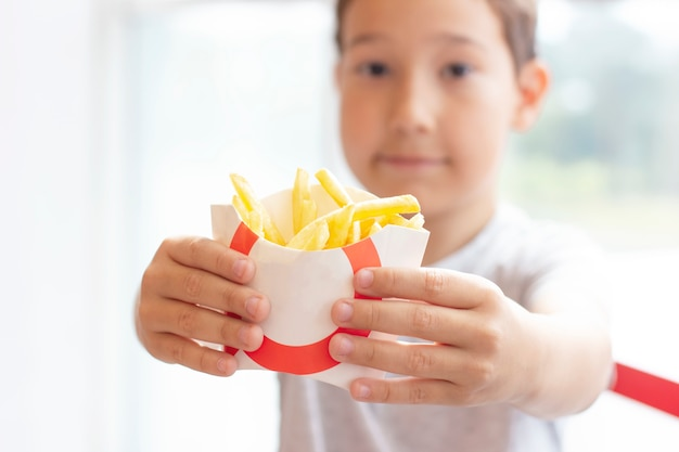The boy 8 years old holds out the fries in paper box, fast food concept
