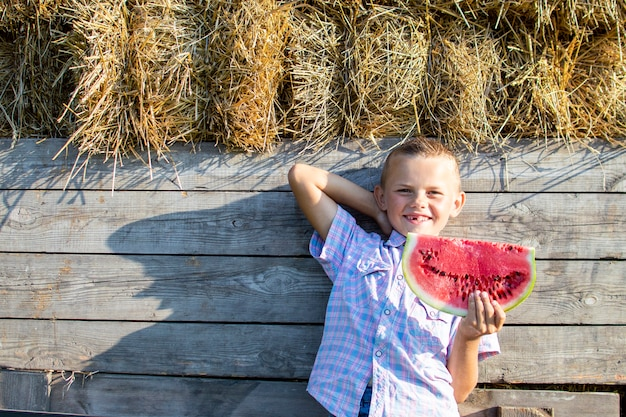 Boy of 8 years old stands in the hayloft in the village and holds a large piece of watermelon