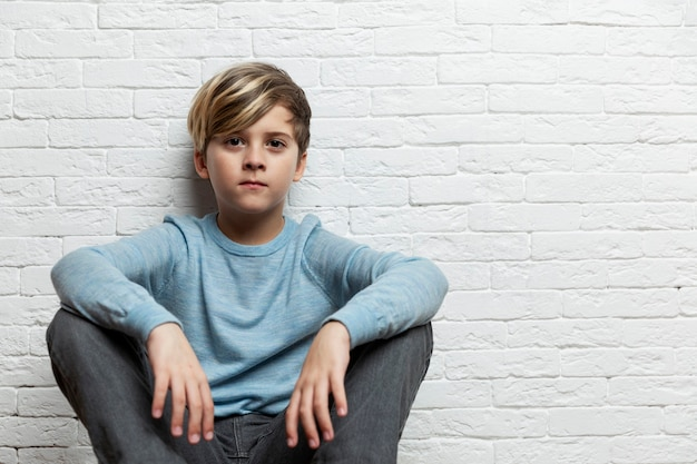 A boy of 9-10 years old sits against a background of a white brick wall. space for text.