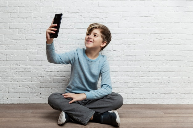 A boy of 9-10 years old sits with a phone in his hands against a background of a white brick wall. online communication and social networks. space for text.