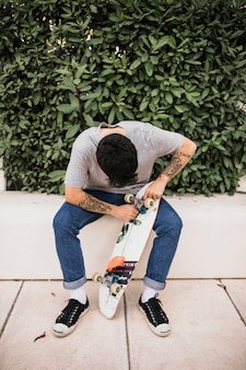 スケートボードの車輪を調整している少年