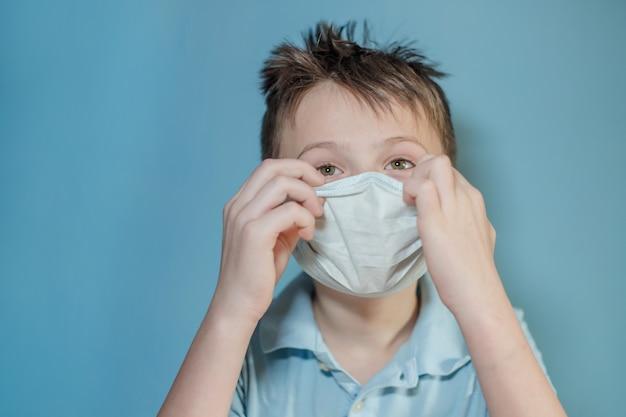 Мальчик корректирует защитную медицинскую маску на лице. ошибки в одевании маски. ребенок касается лица и несет вирус. ребенок с гриппом или простудой защищен от вирусов среди пациентов с коронавирусом