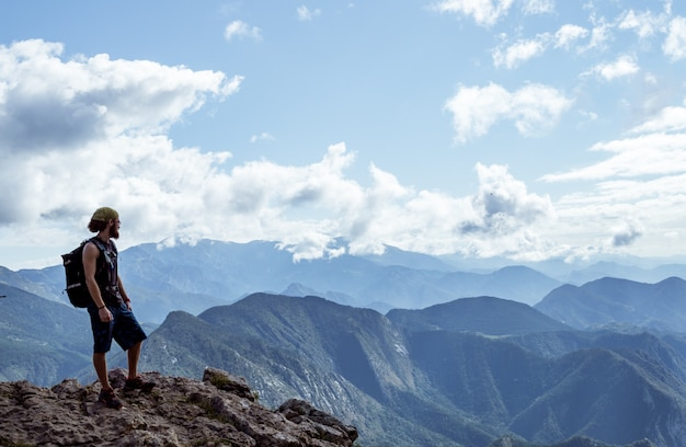 Boy alone on a mountain looking at the horizon