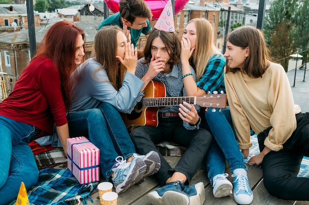 파티에서 충격적인 소식을 듣고 놀란 소년. 험담하는 소녀들. 놀라운 소문