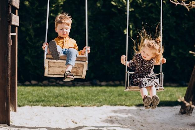 Мальчик и девочка веселятся на качелях