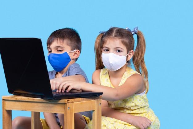 보호용 마스크를 쓰고 온라인 교육을 받는 소년과 소녀가 파란색 배경에 있는 노트북과 함께 작업하고 있습니다.